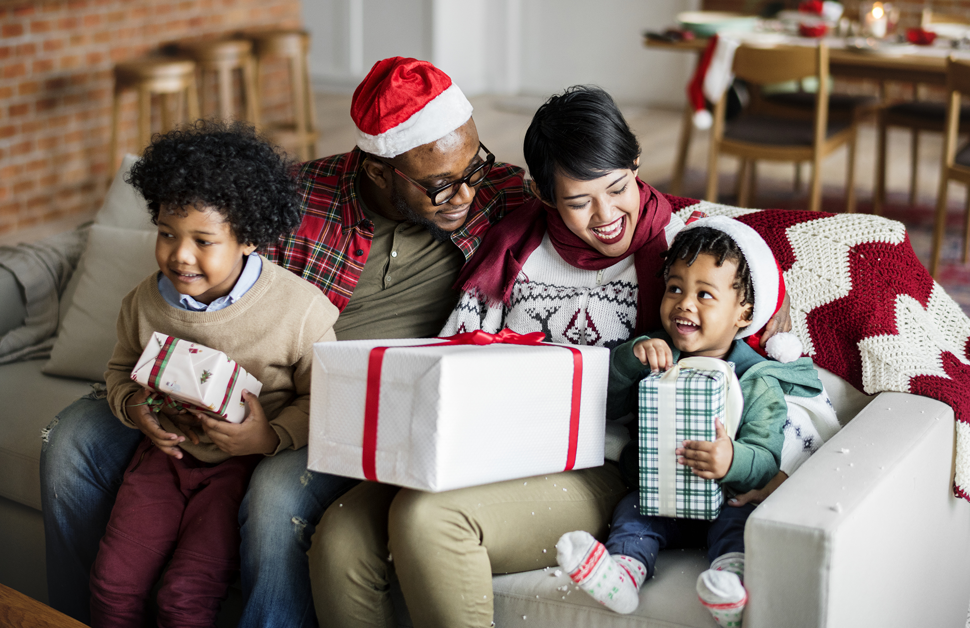a mother, father, and 2 young children sit on the couch as a family, wearing santa hats and holding wrapped gifts in their laps, looking like a happy family enjoying a calm Christmas without stress, meltdowns, or tantrums
