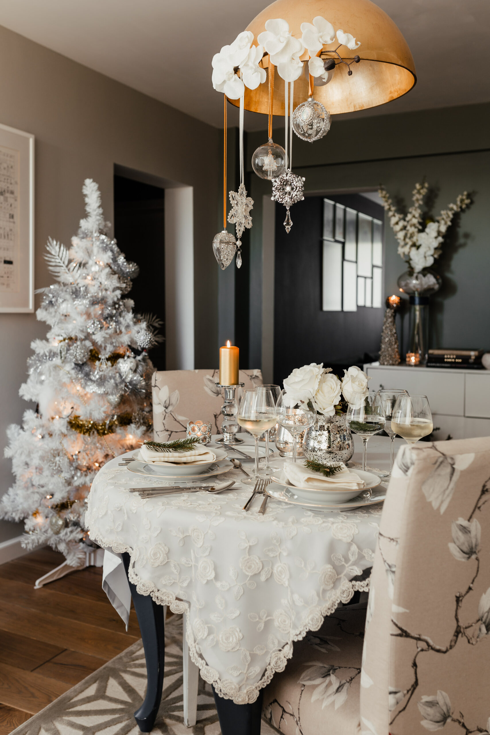 photo of a dining room beautifully decorated for the holidays in a snow white theme with a white Christmas tree, white table cloth, and white decorations, representing a calm, stress-free holiday season without meltdowns or stress