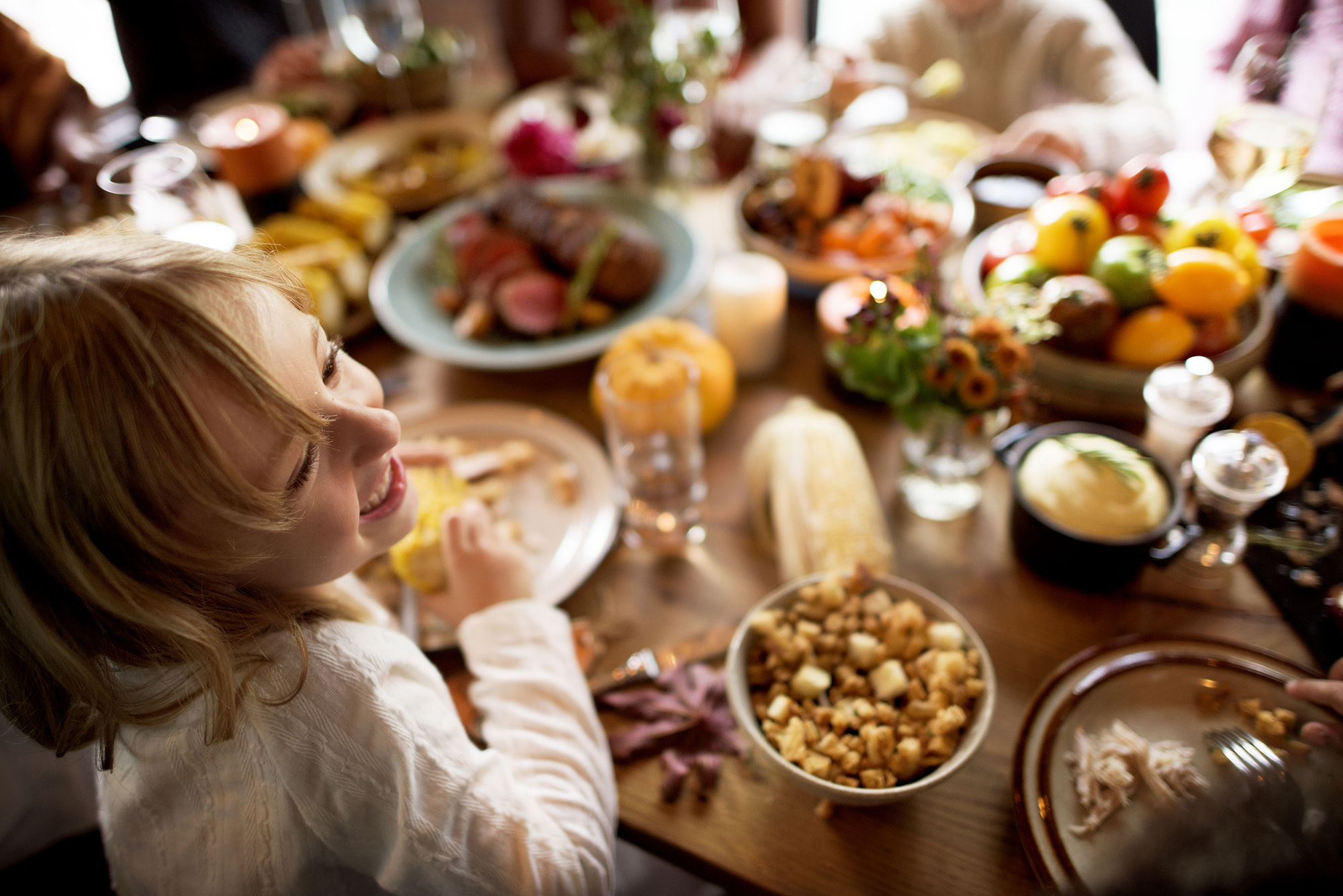 a child enjoying a GAPS diet and anti-inflammatory holiday meal with family. The table is covered in delicious and tasty-looking main dishes and side dishes and everyone is smiling and having fun.