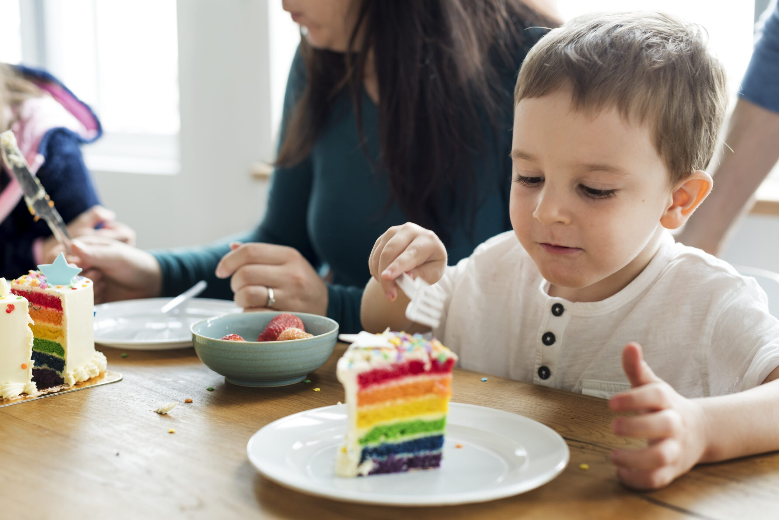 a young boy is about to take a bite from a tall piece of rainbow-coloured cake which represents the harmful effects of sugar that leads to meltdowns and tantrums