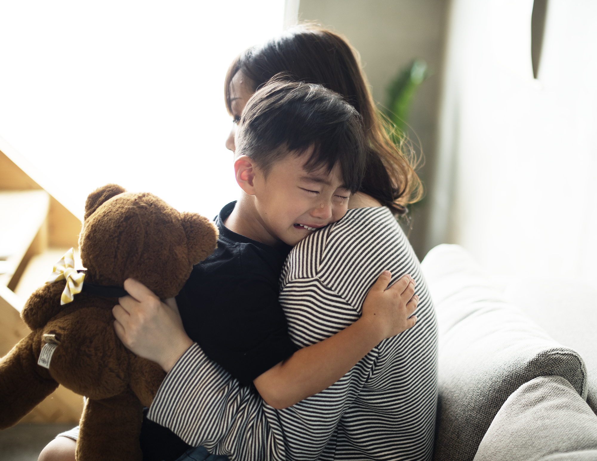 A mother hugs her crying son as he has an emotional meltdown and she is left wondering what caused it