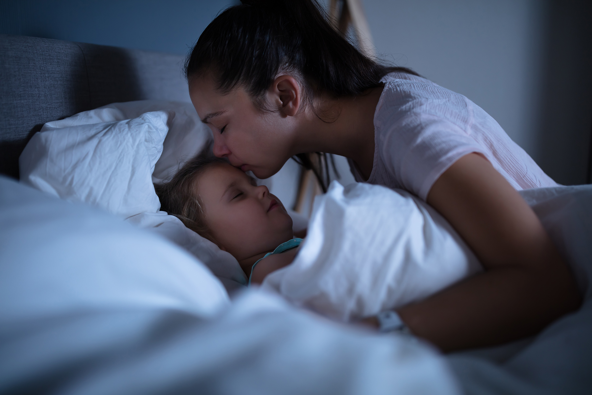 photo of a woman tucking her child into bed and kissing her child's forehead representing bedtime without stress, tears, or tantrums