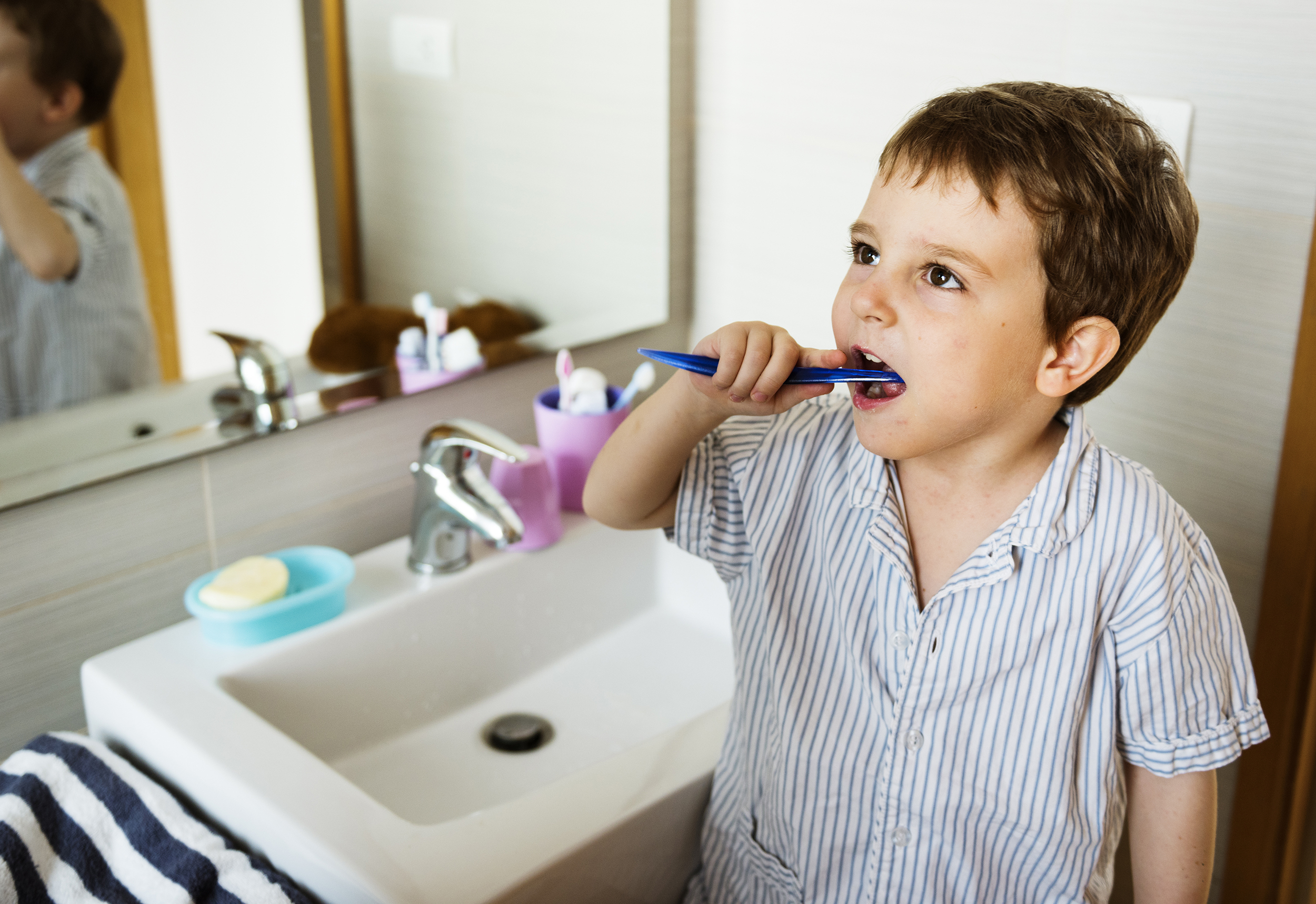 a young boy brushing his teeth next to the bathroom sink using all natural toothpaste and mouthwash to reduce the symptoms of PANS and PANDAS pediatric condition