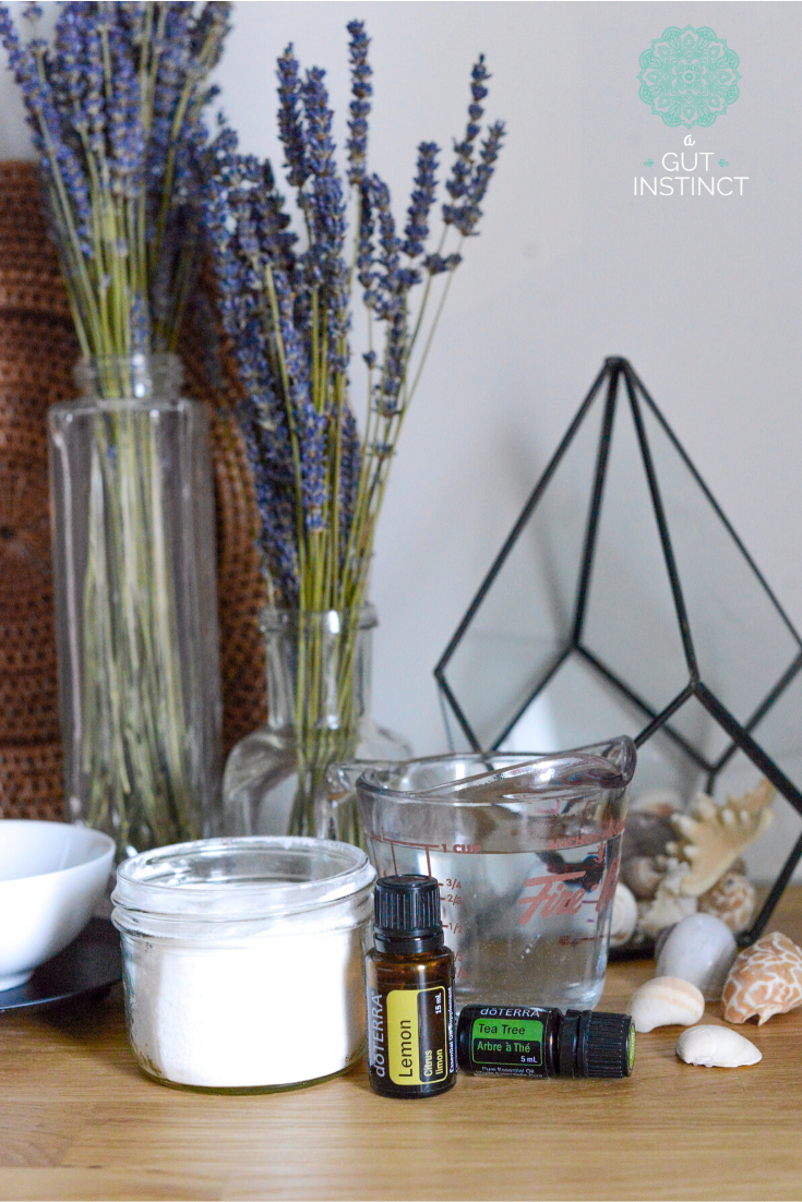 a photo of essential oil bottles, measuring cup, seashells, and vases filled with lavender flowers representing clean and healthy product choices for living in a nontoxic home