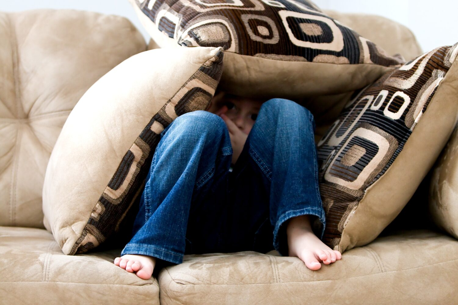 a child hiding under a stack of pillows on the couch because he or she is overwhelmed and has anxiety about the world as a result of a PANS-PANDAS diagnosis or another learning difficulty.