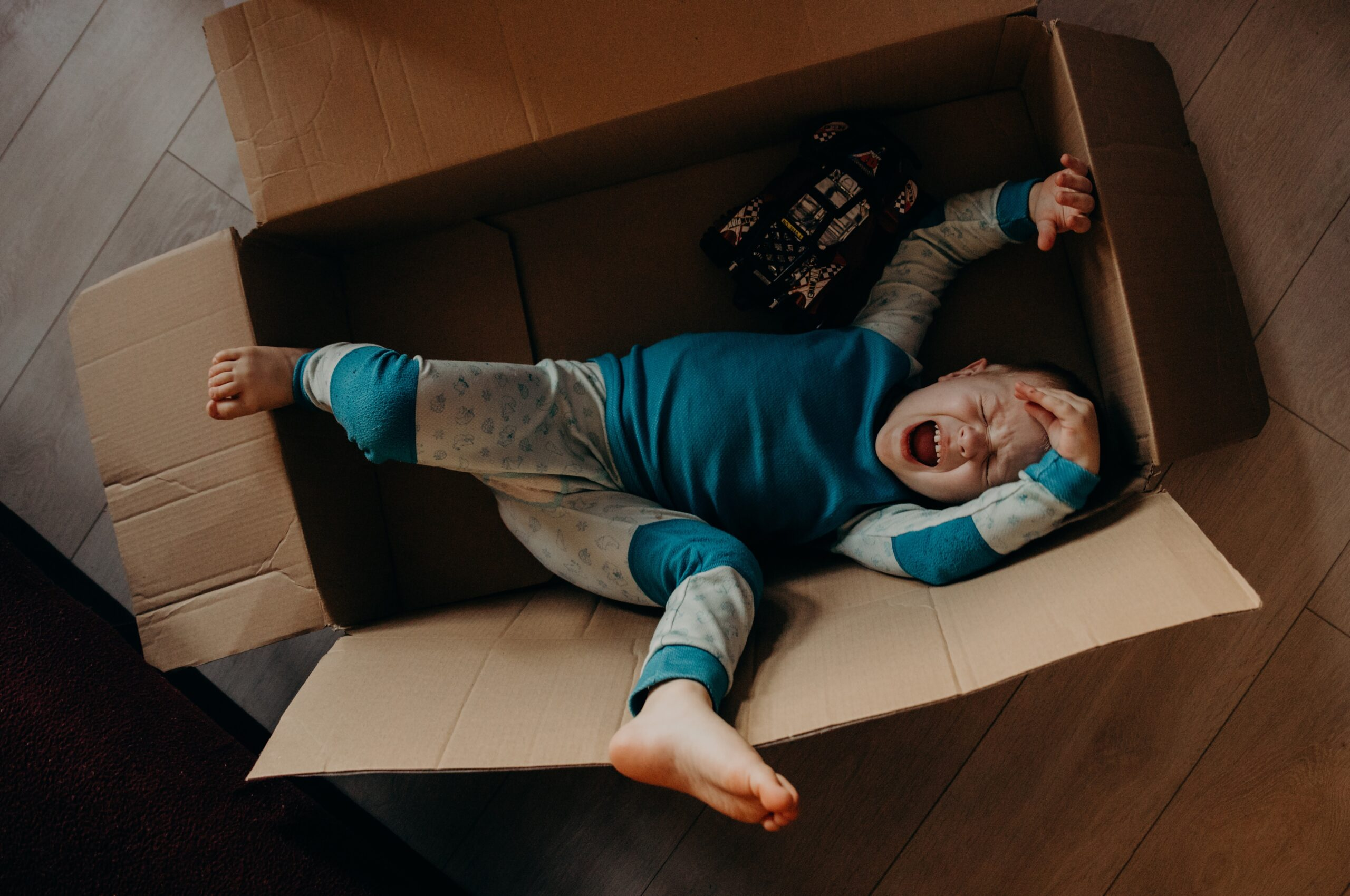 a child having a tantrum meltdown inside a cardboard box representing the kind of behaviour many children with a PANS-PANDAS diagnosis exhibit
