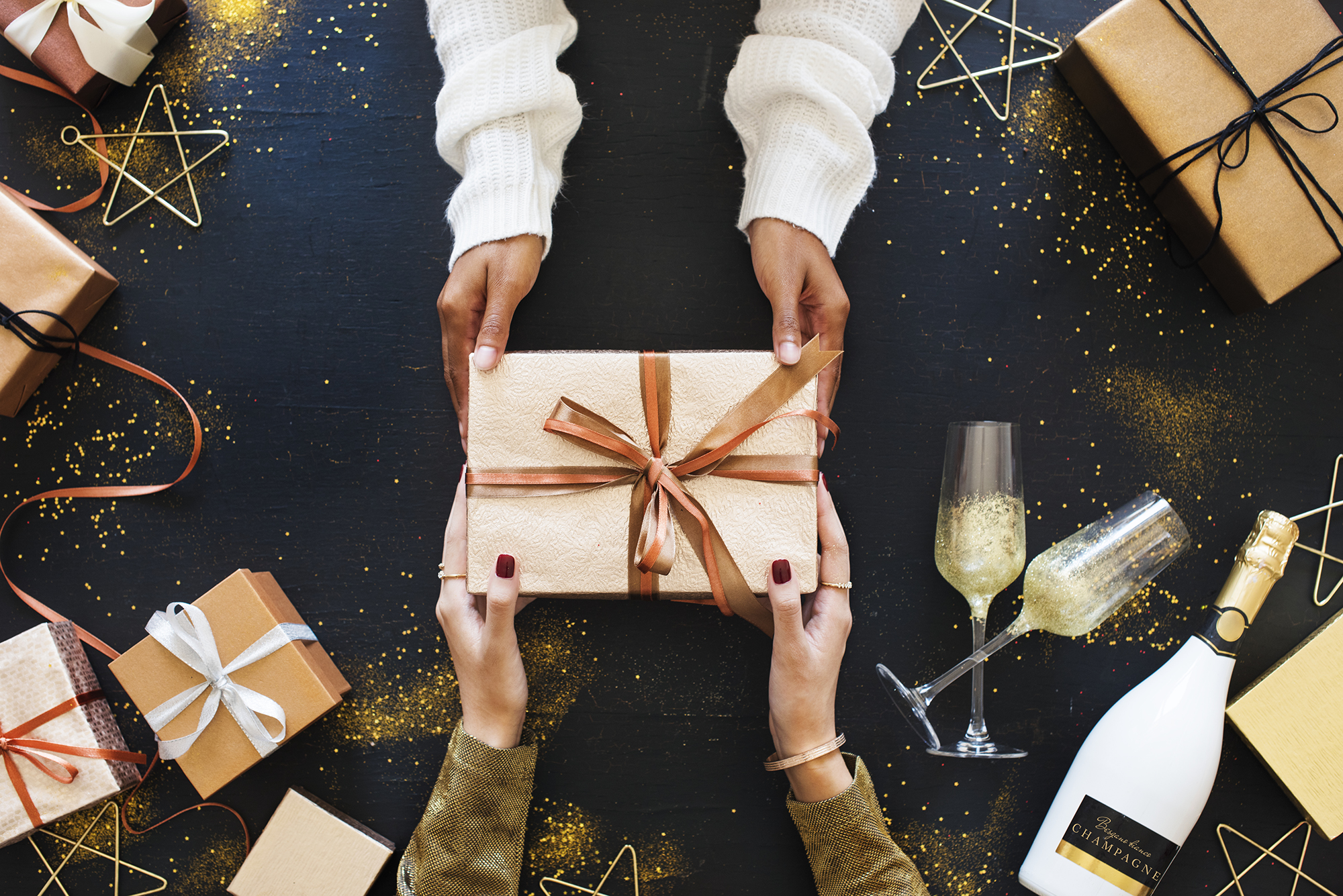 flatlay photo of a pair of hands coming from the top of the photo, handing a gift-wrapped present to a pair of hands coming from the bottom of the photo and they are surrounded by holiday gifts wrapped with bows and ribbons, gold stars, a bottle of champagne, and gold glitter.